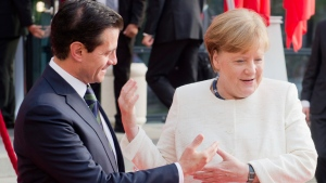 German chancellor Angela Merkel, right, greets Mexico's President Enrique Pena Nieto, as they arrive for the opening of the Hannover Fair, in Hannover, Germany, Sunday, April 22, 2018. (Hauke-Christian Dittrich/dpa via AP)