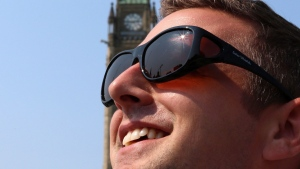 Francis Drouin, M.P. for Glengarry-Prescott-Russell a rural riding outside of Ottawa, views the solar eclipse on Parliament Hill, using solar viewing glass recommended by the Canadian Association of Optometrists Monday, August 21, 2017. THE CANADIAN PRESS/Fred Chartrand