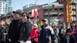 People watch a video feed in an overflow outdoor area as Vancouver Mayor Gregor Robertson delivers an apology on behalf of the city for past discrimination against residents of Chinese descent, during a special city council meeting in Chinatown, in Vancouver, B.C., on Sunday April 22, 2018. The apology acknowledges wrongdoings in legislation, regulations and policies of previous Vancouver city councils. (THE CANADIAN PRESS / Darryl Dyck)
