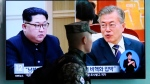 FILE - In this April 18, 2018 file photo, a South Korean marine soldier walks by a TV screen showing file footage of South Korean President Moon Jae-in and North Korean leader Kim Jong Un, left, during a news program at the Seoul Railway Station in Seoul, South Korea. (AP Photo/Ahn Young-joon, File)
