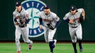 In this April 17, 2018, file photo, Houston Astros outfielders Josh Reddick, left, George Springer and Jake Marisnick race to the infield after they defeated the Seattle Mariners in a baseball game in Seattle. (AP Photo/Elaine Thompson)