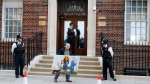 Police officers look on as artist Kaya Mar holds a painting as he walks past the Lindo wing at St Mary's Hospital in London London, Monday, April 23, 2018. (AP/Frank Augstein)