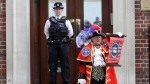 Town Crier Tony Appleton announces that the Duchess of Cambridge has given birth to a baby boy outside the Lindo wing at St Mary's Hospital in London London, Monday, April 23, 2018. Kensington Palace says the Duchess of Cambridge has given birth to her third child, a boy weighing 8 pounds, 7 ounces (3.8 kilograms). (AP Photo/Kirsty Wigglesworth)
