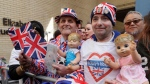 Royal fans John Loughrey, right, and Terry Hutt pose for a photo opposite the Lindo wing at St Mary's Hospital in London London, Monday, April 23, 2018. Kensington Palace says Prince William's wife, the Duchess of Cambridge has entered a London hospital to give birth to the couple's third child. (AP Photo/Kirsty Wigglesworth)