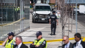 Police are seen near a damaged van in Toronto after a van mounted a sidewalk crashing into a number of pedestrians on Monday, April 23, 2018. (THE CANADIAN PRESS/Aaron Vincent Elkaim)
