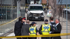 Police are seen near a damaged van in Toronto after a van mounted a sidewalk crashing into a number of pedestrians on Monday, April 23, 2018. THE CANADIAN PRESS/Aaron Vincent Elkaim