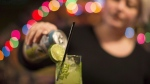 Bar owner Rachel Conduit makes a drink in a glass containing a plastic straw in Toronto's Farside bar on December 5, 2017. (THE CANADIAN PRESS/Chris Young)