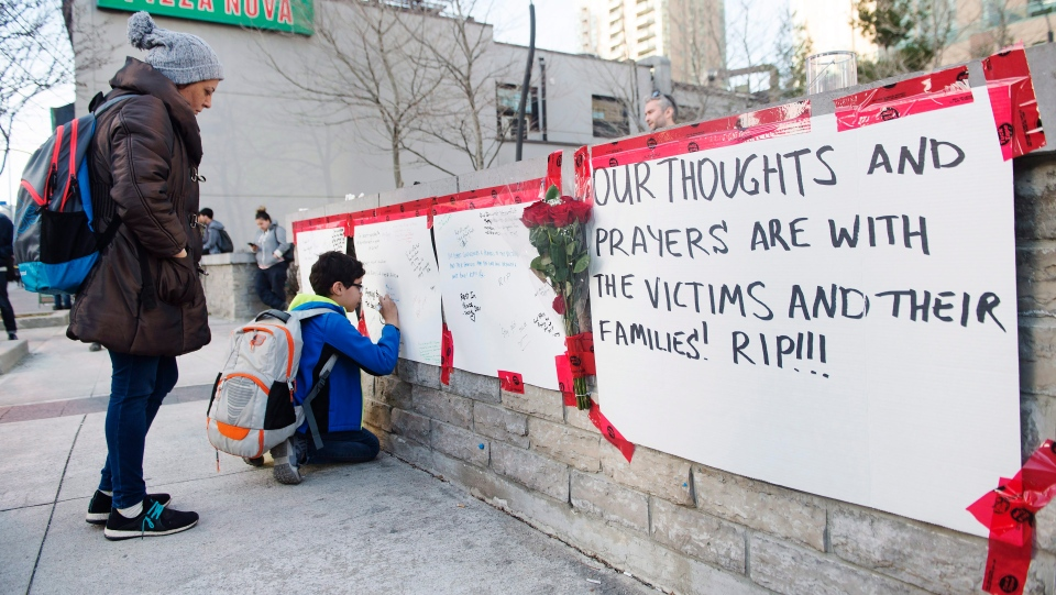 People sign a memorial in Toronto after a van mounted a sidewalk crashing into a number of pedestrians on Monday, April 23, 2018. (THE CANADIAN PRESS/Nathan Denette)
