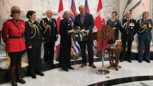 B.C. Premier John Horgan presents outgoing Lt.-Gov. Judith Guichon with a saddle pad for her horse in Victoria on Monday, April 23, 2018. THE CANADIAN PRESS/Dirk Meissner