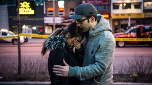 Farzad Salehi consoles his wife Mehrsa Marjani who was is a nearby cafe and witnessed the aftermath when a van hit a number of pedestrians on Yonge Street and Finch in Toronto on Monday, April 23, 2018. Ten people died and 15 others were injured when a van mounted a sidewalk and struck multiple pedestrians along a stretch of one of Toronto's busiest streets. (THE CANADIAN PRESS/Aaron Vincent Elkaim)