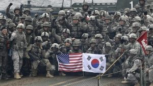 U.S. and South Korean army soldiers pose on a floating bridge on the Hantan river during a joint military exercise against a possible attack from North Korea, in Yeoncheon, South Korea on Dec. 10, 2015. (AP Photo/Ahn Young-joon)
