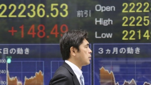 A man walks by an electronic stock board of a securities firm in Tokyo, Tuesday, April 24, 2018. (AP Photo/Koji Sasahara)