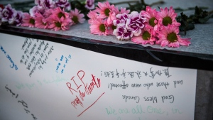 People deliver flowers and write their condolences on a memorial to the victims after a van hit a number of pedestrians on Yonge Street and Finch in Toronto on Monday, April 23, 2018. THE CANADIAN PRESS/Aaron Vincent Elkaim
