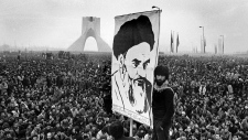In this Dec. 10, 1978 file photo of exiled Muslim leader Ayatollah Khomeini overshadows huge anti-Shah demonstration at the Shahyad monument commemorating 25 years of the monarch's rule and symbol of his power, in Tehran, Iran.  (AP /Michel Lipchitz)