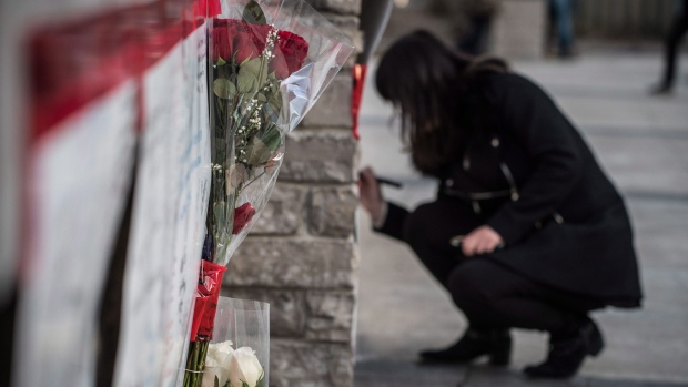 People deliver flowers and write their condolences on a memorial to the victims after a van hit a number of pedestrians on Yonge Street and Finch in Toronto on Monday, April 23, 2018. Ten people died and 15 others were injured when a van mounted a sidewalk and struck multiple pedestrians along a stretch of one of Toronto's busiest streets. THE CANADIAN PRESS/Aaron Vincent Elkaim