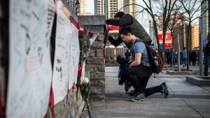 People deliver flowers and write their condolences on a memorial to the victims after a van hit a number of pedestrians on Yonge Street and Finch in Toronto on Monday, April 23, 2018. (THE CANADIAN PRESS/Aaron Vincent Elkaim)