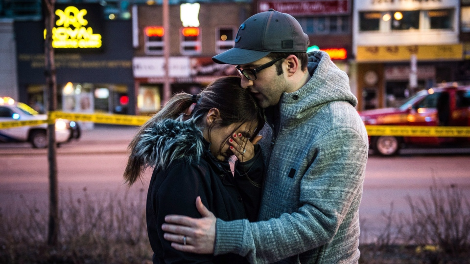 Farzad Salehi consoles his wife Mehrsa Marjani who was is a nearby cafe and witnessed the aftermath when a van hit a number of pedestrians on Yonge Street and Finch in Toronto on Monday, April 23, 2018. (THE CANADIAN PRESS/Aaron Vincent Elkaim)