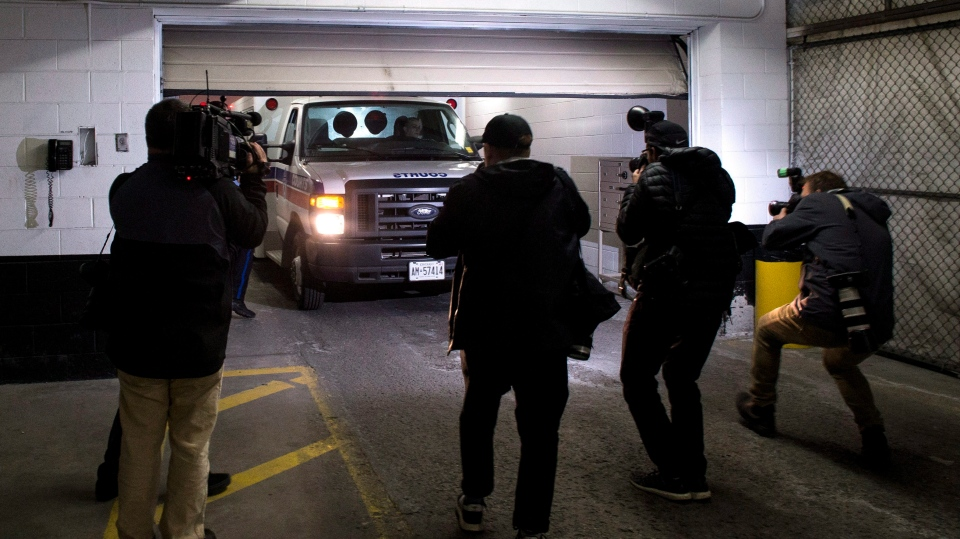 Members of the media follow a court services van as it backs into a courthouse in Toronto on Tuesday, April 24, 2018. (THE CANADIAN PRESS/Chris Young)