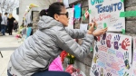 A woman writes a note at a memorial on Yonge Street the day after a driver drove a rented van down sidewalks Monday afternoon, striking pedestrians in his path in Toronto, Tuesday, April 24, 2018. THE CANADIAN PRESS/Galit Rodan