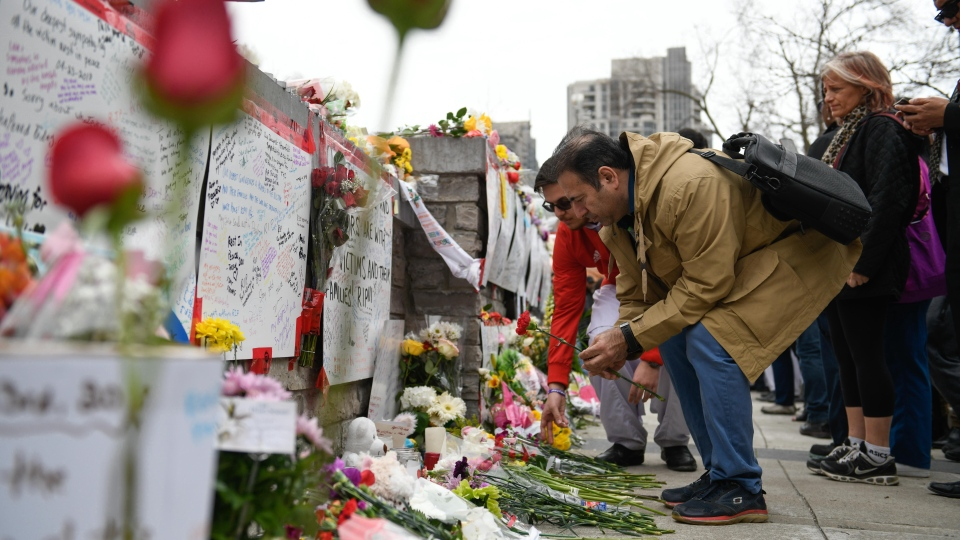 People leave flowers at a memorial on Yonge Street the day after a driver drove a rented van down sidewalks Monday afternoon, striking pedestrians in his path in Toronto, Tuesday, April 24, 2018. (THE CANADIAN PRESS/Galit Rodan)