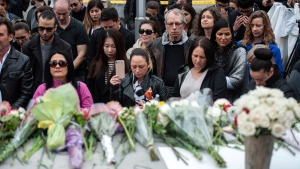 A crowd observes a moment of silence at a memorial on Yonge Street the day after a driver drove a rented van down sidewalks Monday afternoon, striking pedestrians in his path in Toronto, Tuesday, April 24, 2018. THE CANADIAN PRESS/Galit Rodan