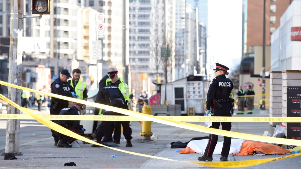 Police secure an area around a covered body in Toronto after a van mounted a sidewalk crashing into a number of pedestrians on Monday, April 23, 2018. (THE CANADIAN PRESS/Nathan Denette)