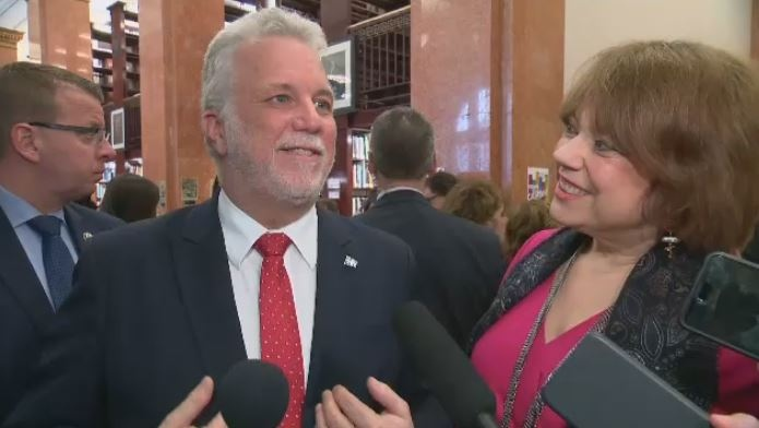 Premier Philippe Couillard answers a question on gender parity as Helene David, minister for the status of women, looks on.