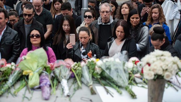 A crowd observes a moment of silence at a memorial on Yonge Street the day after a driver drove a rented van down sidewalks Monday afternoon, striking pedestrians in his path in Toronto, Tuesday, April 24, 2018. (THE CANADIAN PRESS/Galit Rodan)