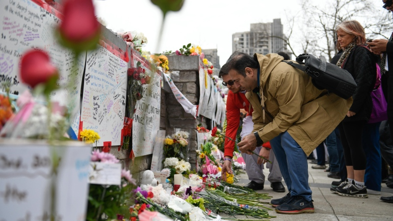 People leave flowers at a memorial on Yonge Street the day after a driver drove a rented van down sidewalks Monday afternoon, striking pedestrians in his path in Toronto, Tuesday, April 24, 2018. THE CANADIAN PRESS/Galit Rodan