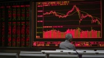 A man monitors stock prices at a brokerage house in Beijing, Monday, April 23, 2018. (AP Photo/Andy Wong)