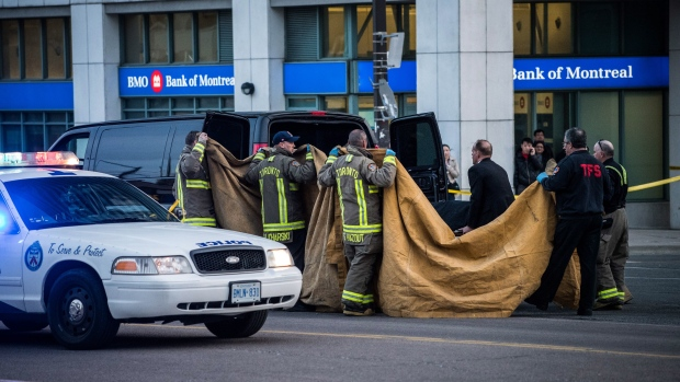 A coroner removes a dead body from the sidewalk after a van hit a number of pedestrians on Yonge Street and Finch in Toronto on Monday, April 23, 2018. Ten people died and 15 others were injured when a van mounted a sidewalk and struck multiple pedestrians along a stretch of one of Toronto's busiest streets. THE CANADIAN PRESS/Aaron Vincent Elkaim