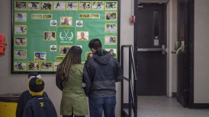 People look at a memorial wall for the Humboldt Broncos in the lobby during game one of the Saskatchewan Junior Hockey league finals between the Estevan Bruins and Nipawin Hawks in Nipawin, Sask., on April 14, 2018. (Liam Richards / THE CANADIAN PRESS)
