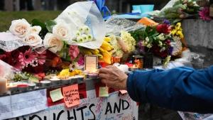 A man lights a candle at a vigil on Yonge Street i