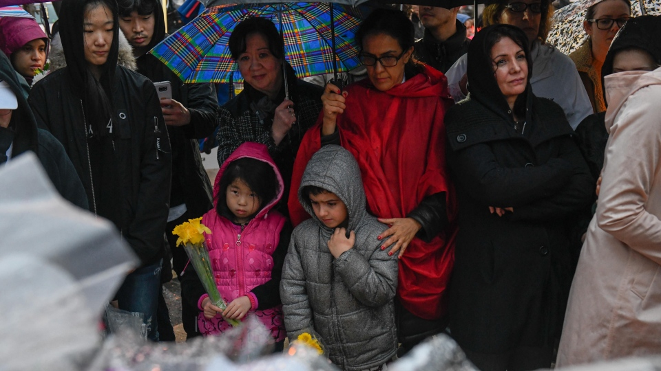Two children hold flowers at a vigil on Yonge Street in Toronto, Tuesday, April 24, 2018. THE CANADIAN PRESS/Galit Rodan