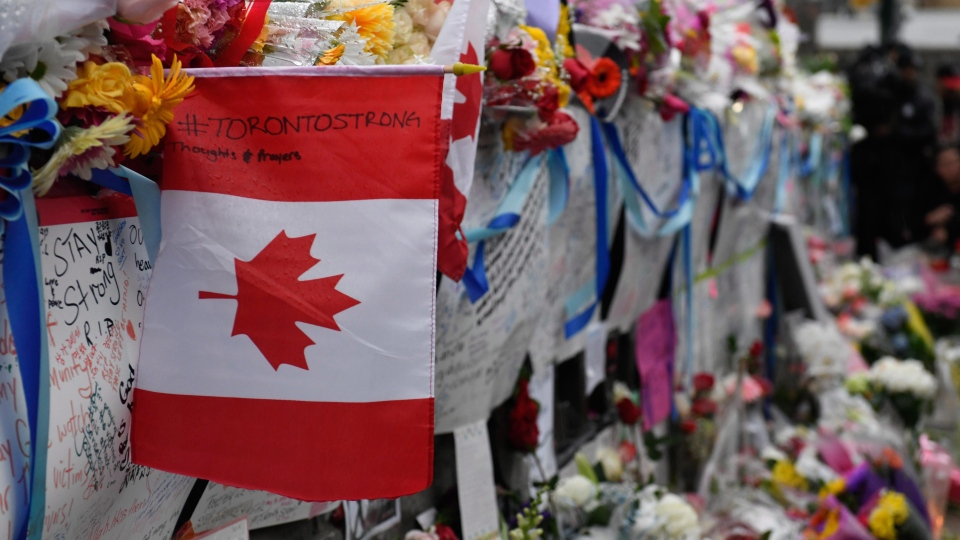 Signs are left at a vigil on Yonge Street in Toronto, Tuesday, April 24, 2018. Ten people were killed and 14 were injured in Monday's deadly attack in which a van struck pedestrians in northern Toronto. THE CANADIAN PRESS/Galit Rodan