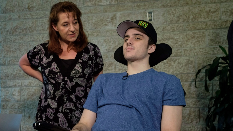Humboldt Broncos hockey player Ryan Straschnitzki, who was paralyzed following a bus crash that killed 16 people, speaks to the media as his mother Michelle, looks on in Calgary, Alta., Wednesday, April 25, 2018. (THE CANADIAN PRESS/Jeff McIntosh)