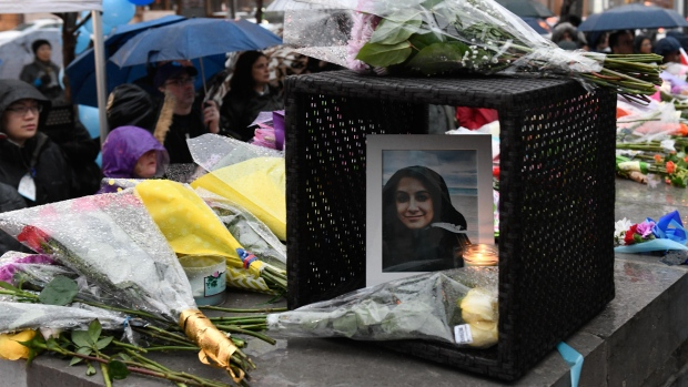 A photo of Anne Marie D'Amico is left at a vigil on Yonge Street in 