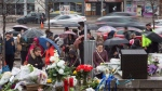People look on at a growing memorial to the victims who died in Monday's deadly van attack along Yonge Street in Toronto on Wednesday, April 25, 2018. THE CANADIAN PRESS/Chris Young