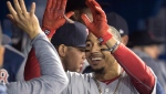 Boston Red Sox's Mookie Betts celebrates in the dugout after hitting a home run in his first at bat against the Toronto Blue Jays in first inning American League MLB baseball action in Toronto on Wednesday April 25, 2018. (THE CANADIAN PRESS/Fred Thornhill)