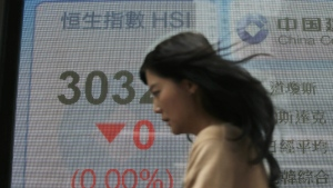 A woman walks past an electronic board showing Hong Kong share index outside a bank in Hong Kong, Thursday, April 26, 2018. (AP Photo/Kin Cheung)