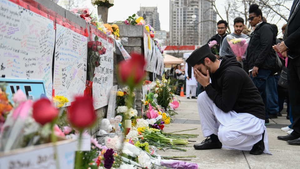 A member of Toronto's Ahmadiyya Muslim community says a silent prayer at a memorial on Yonge Street, on April 24, 2018. (Galit Rodan / THE CANADIAN PRESS)