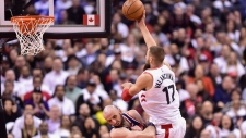 Toronto Raptors' Jonas Valanciunas shots over Washington Wizards' Marcin Gortat during second half game five of round one NBA playoff basketball action in Toronto on Wednesday, April 25, 2018. THE CANADIAN PRESS/Frank Gunn