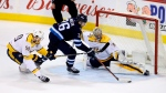In this March 25, 2018, file photo, Nashville Predators' Roman Josi (59) tries to stop Winnipeg Jets' Blake Wheeler (26) as he gets a scoring attempt on goaltender Juuse Saros (74) during the overtime period of NHL hockey action in Winnipeg, Manitoba. (Trevor Hagan/The Canadian Press via AP, File)