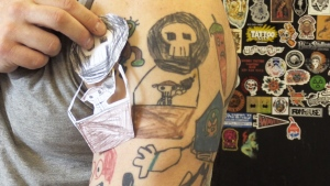 Craig Sears displays tattoos based on his son's drawings. (CTV Kitchener)