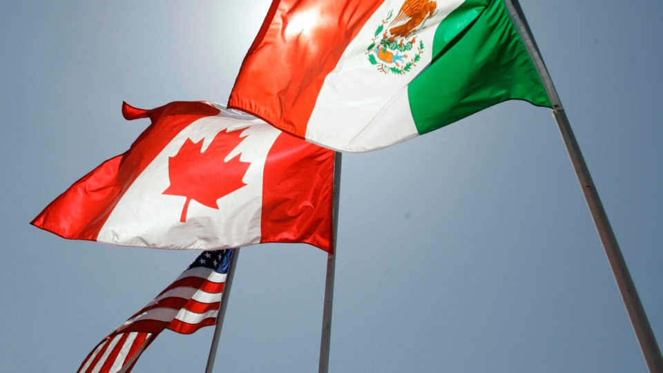 In this April 21, 2008 file photo, national flags of the United States, Canada, and Mexico fly in the breeze in New Orleans. THE CANADIAN PRESS/AP/Judi Bottoni