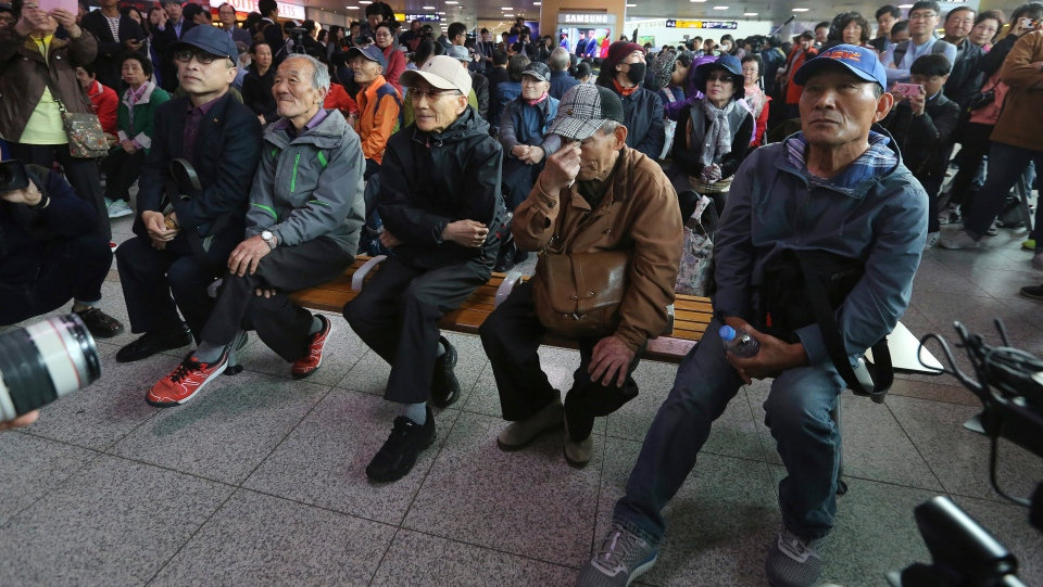 A South Korean man, second from right, wipes tears as people watch a TV screen showing the live broadcast of South Korean President Moon Jae-in meeting with North Korean leader Kim Jong Un at the border village of Panmunjom during a news program at the Seoul Railway Station in Seoul, South Korea, Friday, April 27, 2018. (AP Photo/Ahn Young-joon)