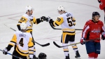 Pittsburgh Penguins center Jake Guentzel (59) celebrates his goal with center Sidney Crosby (87) and defenseman Justin Schultz (4) during the third period in Game 1 of an NHL second-round hockey playoff series as Washington Capitals right wing T.J. Oshie (77) skates away Thursday, April 26, 2018, in Washington.  (AP Photo/Nick Wass)