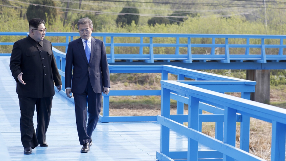North Korean leader Kim Jong Un, left, and South Korean President Moon Jae-in talk as they walk in Panmunjom in the DMZ, South Korea, on April 27, 2018. (Korea Summit Press Pool via AP)