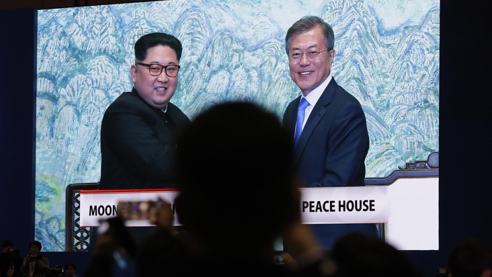 A huge screen shows live video of North Korean leader Kim Jong Un and South Korean President Moon Jae-in at a press centre for the inter-Korean summit in Goyang, South Korea, on April 27, 2018. (Lee Jin-man / AP)