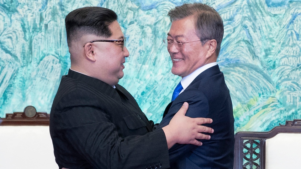 North Korean leader Kim Jong Un, left, and South Korean President Moon Jae-in embrace each other after signing on a joint statement at the border village of Panmunjom in the Demilitarized Zone, South Korea, Friday, April 27, 2018. (Korea Summit Press)